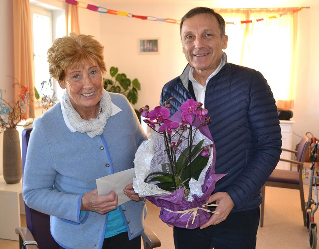 Bürgermeister überreicht Jubilarin der Tagespflege ein Blumengeschenk