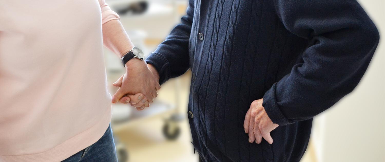 Gerontofachkraft nimmt Senior an die Hand