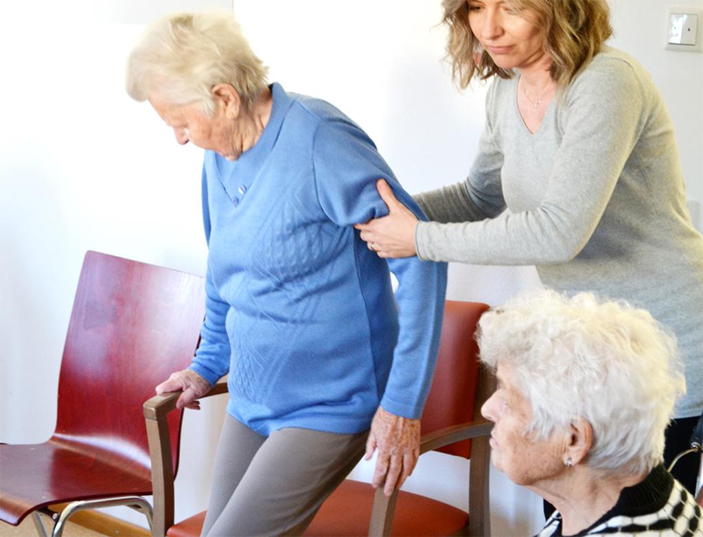 Pflegekraft unterstützt Seniorin