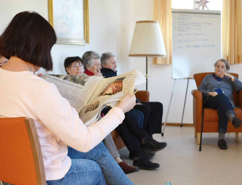 Geronofachkraft liest Senioren aus der Tageszeitung vor