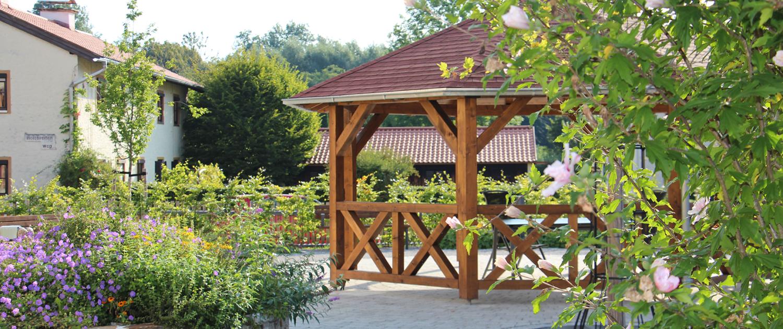 Von Büschen und Blumenhochbeet umgebener Holzpavillon mit Sitzgelegenheiten